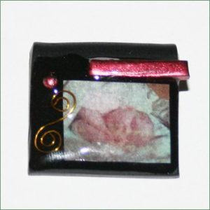 Sort cernithalskæde med babybillede, rødt pynt og en lille guldsnor, dækket med resin