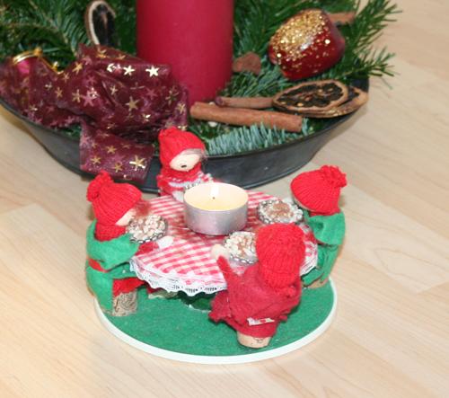 Hyggelig julepynt: Bord med fire nisser, der spiser risengrød. Midt på bordet står et fyrfadslys.