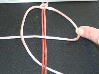 Knyttet armbånd trin 7: Før venstre snor hen over højre snor og ned under midtersnorene